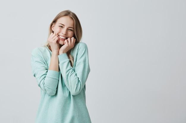 Schattige blonde vrouw met lichtgevende donkere ogen, stralend gezicht en zachte glimlach die haar succes verheugen.