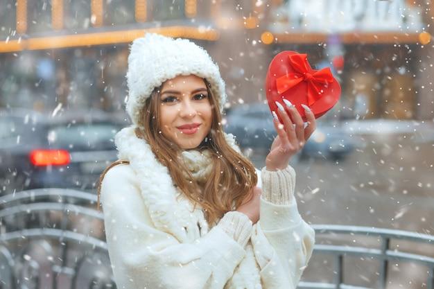 Schattige blonde vrouw met rode geschenkdoos, wandelen in de stad tijdens de sneeuwval