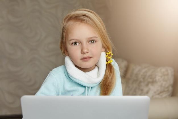 Schattige blonde vrouwelijke schooljongen met slordige paardenstaart genieten van vrije tijd thuis