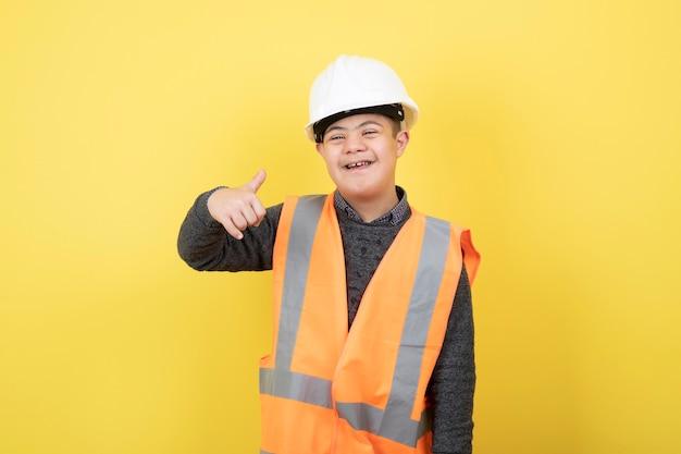 Schattige bouwvakker in veiligheidsvest duimen opgevend.