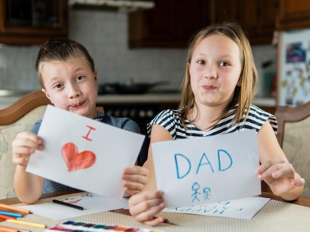Schattige broer en zus tekenen voor vaderdag