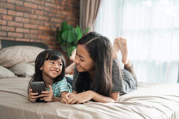 Schattige broer of zus met behulp van mobiele telefoon samen