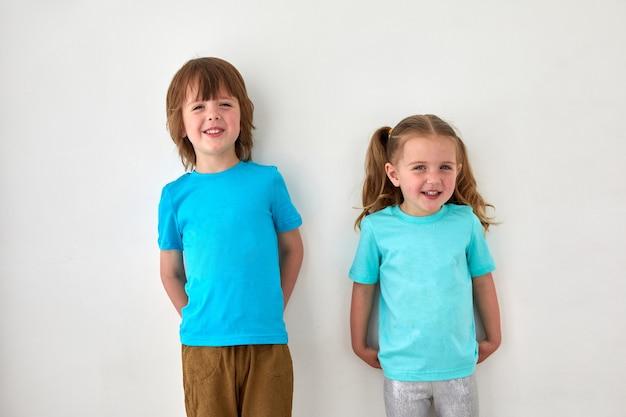 Schattige broers en zussen in blauwe t-shirts tegen grijze muur