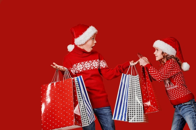 Schattige broers en zussen in rode trui met boodschappentassen