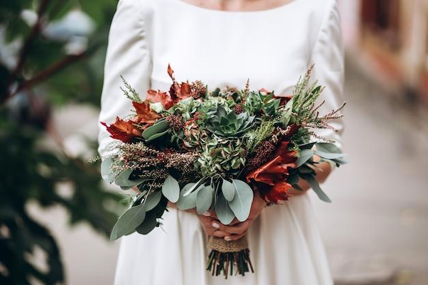 Schattige bruid met een herfst boeket.