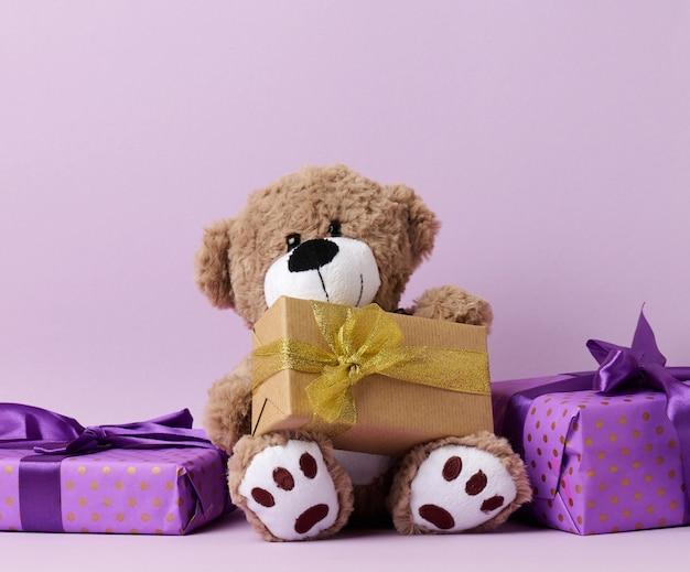 Schattige bruine teddybeer en doos verpakt in papier en zijden lint op een paarse achtergrond. prijs en gefeliciteerd
