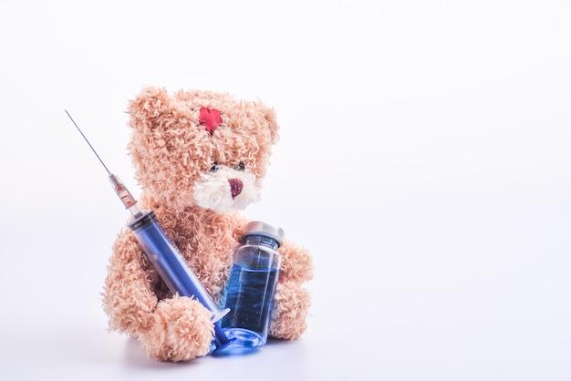 Schattige bruine teddybeer en medische flacon of ampullen voor injectie en spuit. blauwe medische flacon en spuit in handen bruine teddybeer. teddybeer met een spuit en een ampul. geïsoleerd. kopieer ruimte