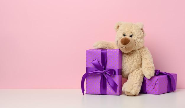 Schattige bruine teddybeer met een doos verpakt in papier en rood zijden lint op witte tafel. prijs en gefeliciteerd, roze achtergrond, kopieer ruimte