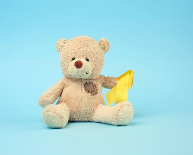 Schattige bruine teddybeer met een patch houdt een zijde geel lint in de vorm van een lus