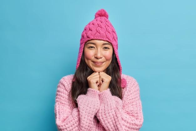 Schattige brunette aziatisch meisje houdt handen onder kin kijkt aangenaam aan voorzijde draagt winter hoed en trui klaar voor wandeling tijdens koude dag geïsoleerd over blauwe muur