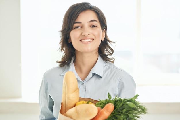 Schattige brunette in de keuken met een pakket gezonde voeding supermarkt