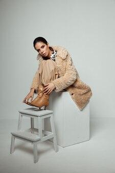 Schattige brunette in herfst kleding bruine laarzen op de stoel accessoires.