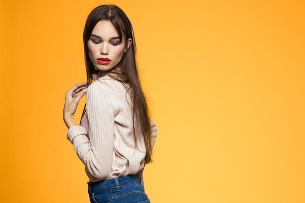 Schattige brunette make-up rode lippen modieuze kleding geel