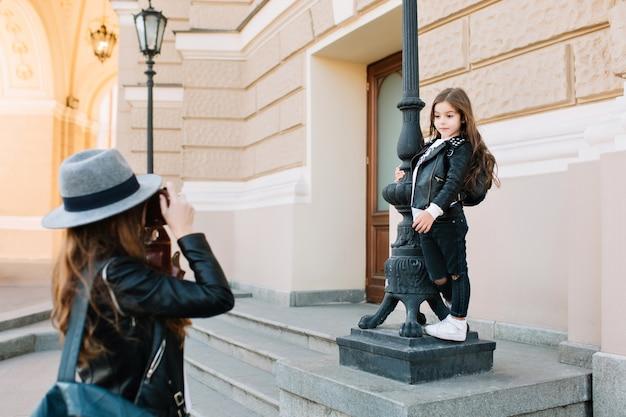 Schattige brunette meisje dragen witte sneakers en denim broek bedrijf door pijler, terwijl moeder nemen foto staan voor haar. elegante jonge vrouw lederen draagtas en camera foto maken.