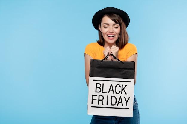 Schattige brunette meisje in hoed en t-shirt zwarte vrijdag paperbag te houden en tevredenheid te uiten
