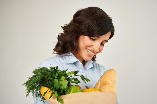 Schattige brunette papieren zak met boodschappen groenten gezond voedsel