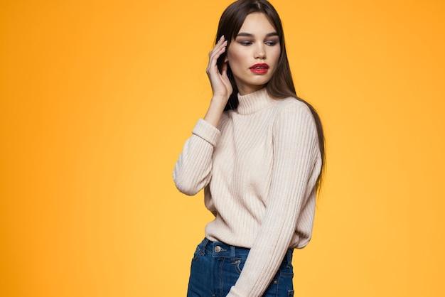 Schattige brunette rode lippen modieuze kleding studio geel.