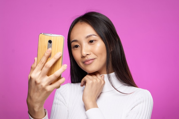 Schattige brunette telefoon in de hand internet technologie levensstijl roze