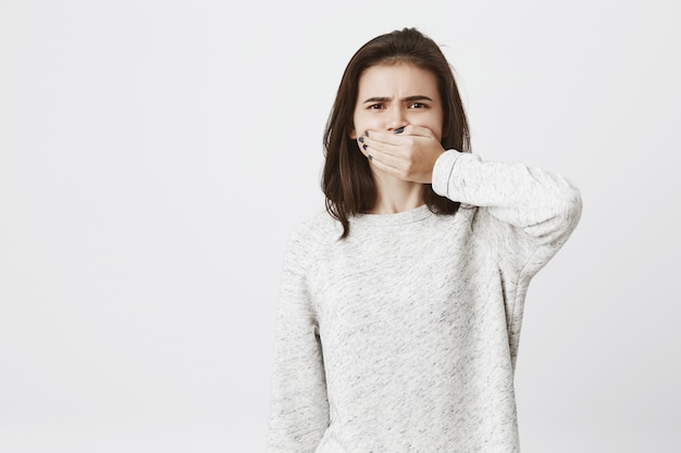 Schattige brunette vrouw bedekt haar mond en drukt afkeer of afkeer uit