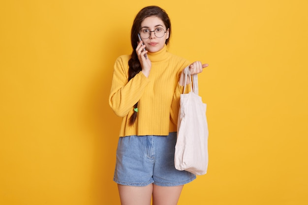 Schattige brunette vrouw met gele trui en korte, zak in de hand houden, praten met haar vriend via moderne smartphone
