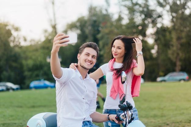 Schattige brunette vrouw speelt met haar lange haren terwijl vriendje een foto van haar maakt