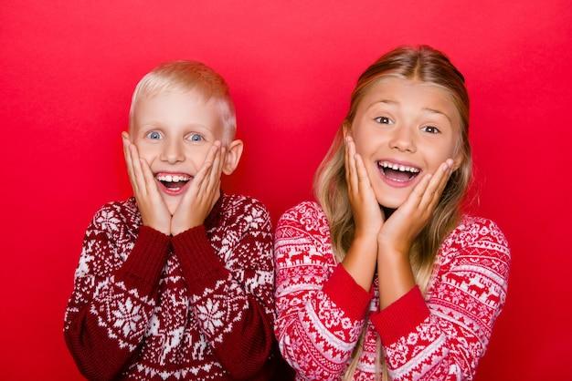 Schattige, charmante kleine familieleden met een stralende glimlach, geschokt door ongelooflijke, onverwachte cadeaus, in traditionele kerstkleding, geïsoleerd op een rode ruimte, gezichten vasthoudend met armpalmen