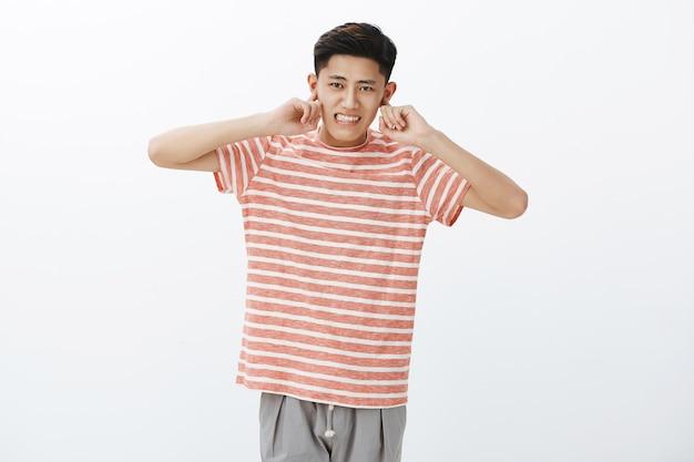 Schattige chinese man die niet gewend is aan het drukke stadsleven oren sluiten met wijsvinger hoort geen luid geluid van files tanden op elkaar klemmen ontevreden
