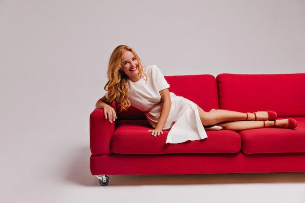 Schattige dame in jurk en hoge hakken liggend op de bank. verfijnd europees meisje poseren in de woonkamer met een glimlach.