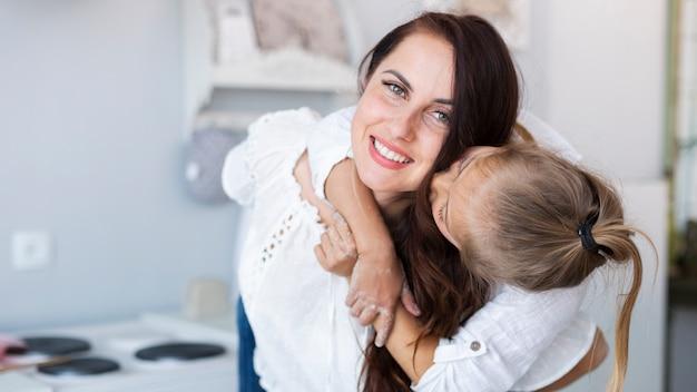 Schattige dochter kust haar moeder