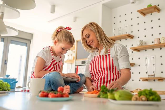 Schattige dochter spelen aan de telefoon terwijl de moeder aan het koken is