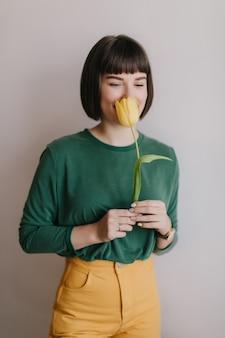 Schattige donkerbruine vrouw die in gele broek van tulpensmaak geniet. portret van gelukkig kortharig meisje snuift bloem.