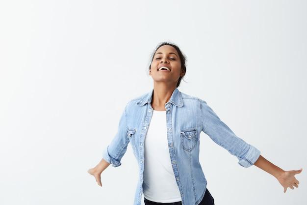 Schattige donkere vrouw in denim shirt met zwart haar glimlachend met witte tanden zelfs tijdens het springen. mensen, oprechte emoties, lifestyle concept