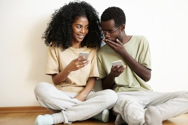 Schattige donkere vrouw met afro-kapsel met sluwe uitdrukking terwijl ze nieuws of roddels deelt met haar geschokte vriend, die met verbazing naar het scherm kijkt