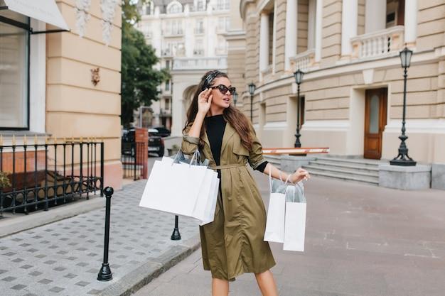 Schattige donkerharige europese vrouw met pakketten in de buurt van winkelcentrum
