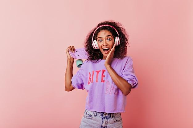 Schattige donkerogige dame in koptelefoon poseren met verbaasde glimlach. leuk afrikaans meisje dat met skateboard verbazing op roze uitdrukt.