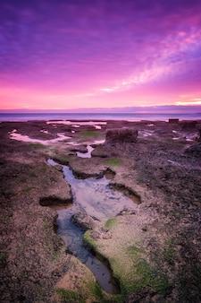 Schattige dramatische zee zonsondergang. in paarse tinten.