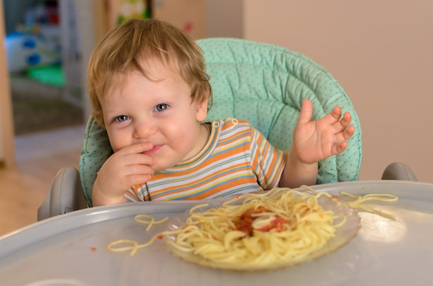 Schattige een jaar oude baby eet spaghetti in een kinderstoel.