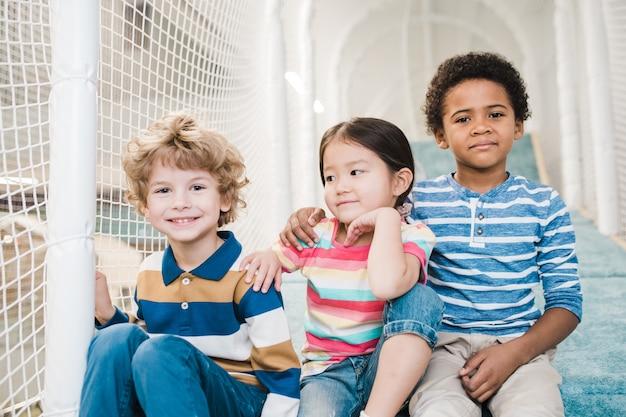 Schattige en aanhankelijke interculturele jongens en meisjes in vrijetijdskleding kwamen samen op de speelruimte in het recreatiecentrum