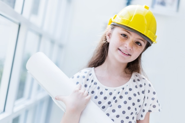 Schattige en mooie blanke meisje is kostuum voor ingenieur carrière met wazige achtergrond