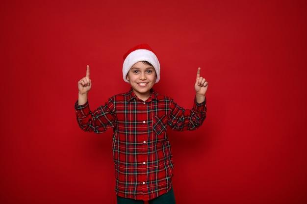 Schattige europese preadolescente vrolijke jongen, knap kind in kerstmuts en geruit hemd wijst met vingers omhoog op een kopieerruimte op rood gekleurde achtergrond voor kerstmis en nieuwjaar advertentie