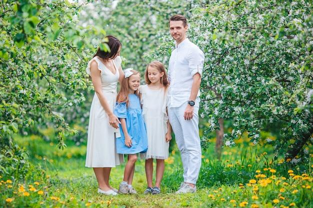 Schattige familie in bloeiende kersen tuin op een mooie lentedag