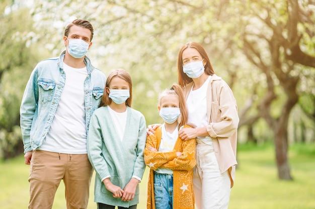 Schattige familie in bloeiende kersentuin in maskers