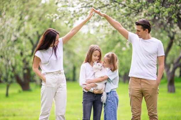 Schattige familie in bloeiende kersentuin op mooie de lentedag