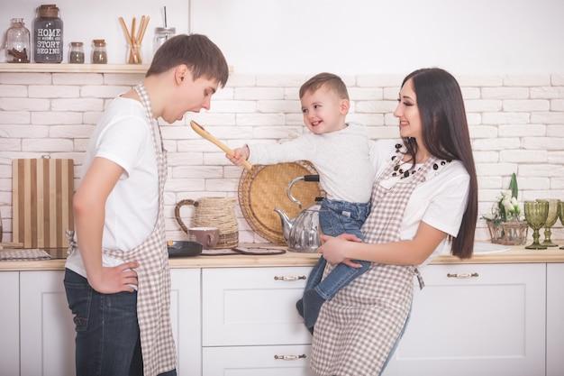 Schattige familie koken samen. jong gezin in de keuken met ontbijt of diner. moeder, vader en hun kleine kind bereiden maaltijd.