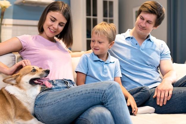 Schattige familie spelen met zoon en hond