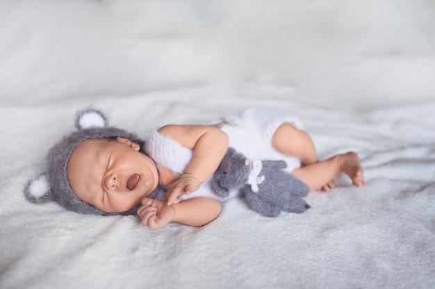 Schattige gapende pasgeboren babyjongen slapen in wieg in een gebreid pak met oren.
