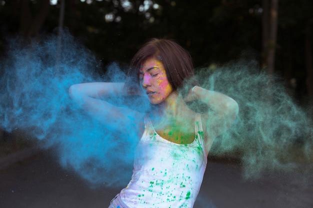 Schattige gebruinde vrouw met kort haar poseren met exploderende holi blauwe en groene droge verf
