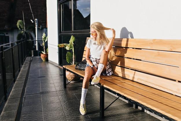 Schattige gelooide vrouw in witte sokken spelen met lang blond haar. openluchtportret van zalig kaukasisch meisje in gele schoenen die op houten bank koelen.