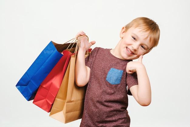 Schattige gelukkig kind met kleurrijke boodschappentassen