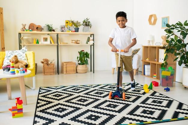 Schattige gelukkig mixed-race kleuter in vrijetijdskleding speelgoed plastic scooter rijden zwart-wit tapijt in woonkamer of kleuterschool